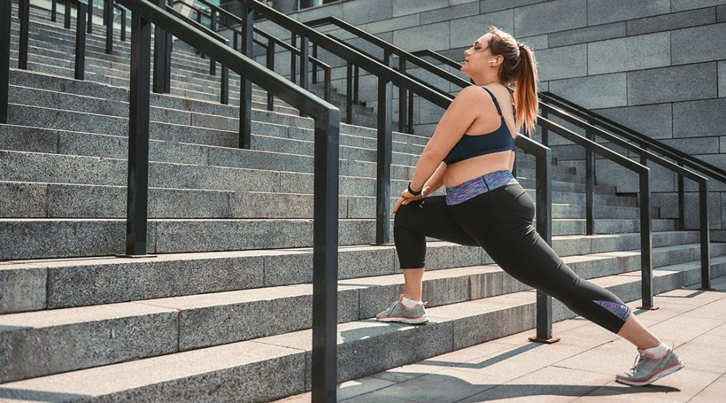 Stretching after great workout. Happy plus size woman in sport clothes doing stretching exercises on the stairs outdoors. Healthy life. Sport concept. Weight losing; blog: Ways to Avoid Workout Injuries
