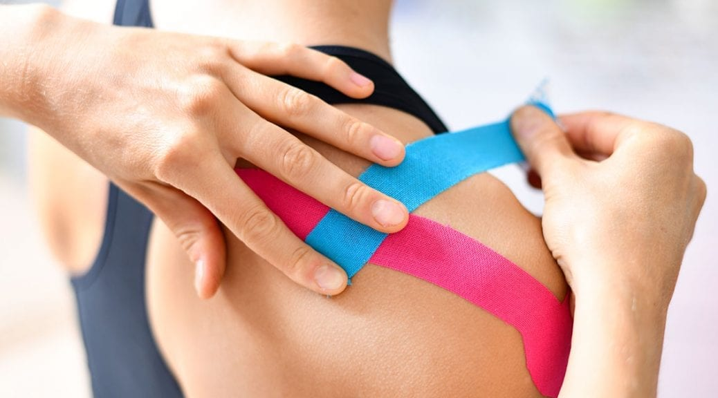 Kinesiology taping treatment with blue and pink tape on athlete patient injured arm. Woman hands apply kinesio treatment after sports muscle injury; blog: 5 Sports Injury Treatments