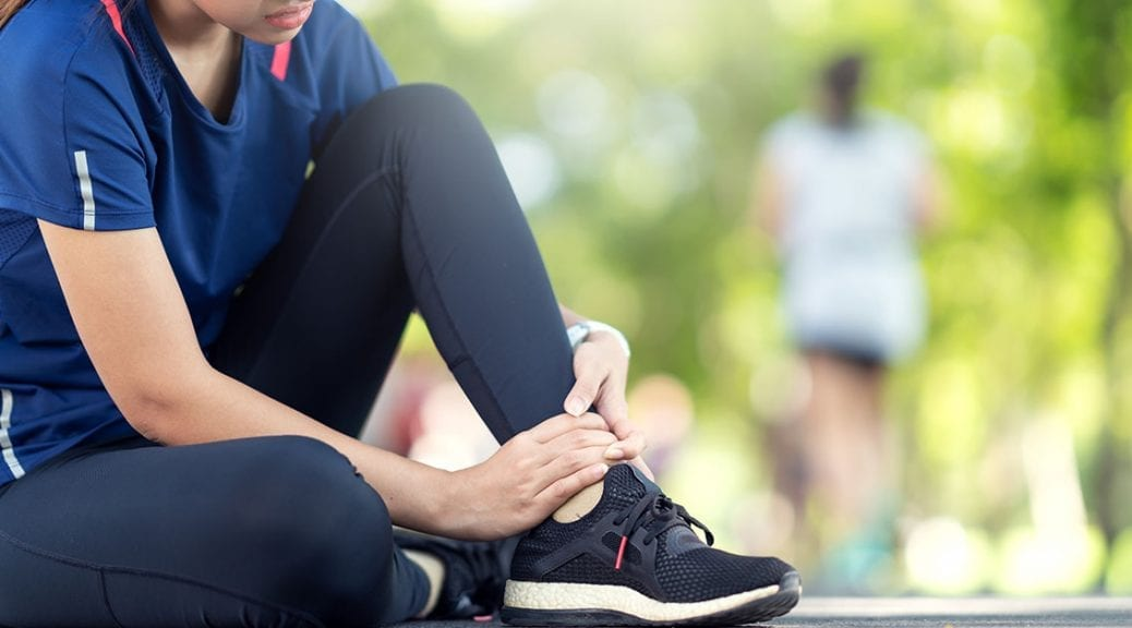 Young asian woman suffering ankle injury. Runner girl is injured by sprain ankle while running or exercising. Female runner touching foot in pain due to sprained ankle. Injury from workout concept; blog: difference between sprains and strains