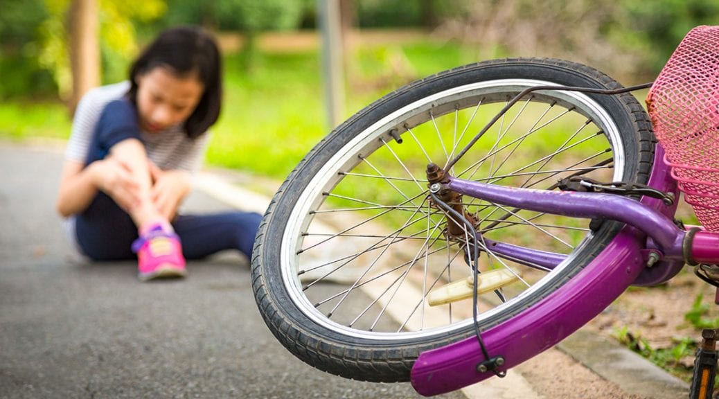 Asian little girl sitting down on the road with a slight sore leg pain due to a falling bicycle accident,the bike fall in front of the child at the park,falling bicycle,Accident concept; blog: 6 Tips for Avoiding Summer Sports Injuries
