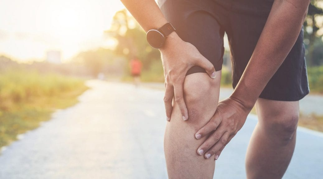 A man on a jog experiencing knee pain