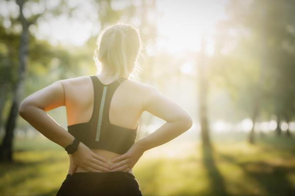 A female jogger experiencing lower back pain